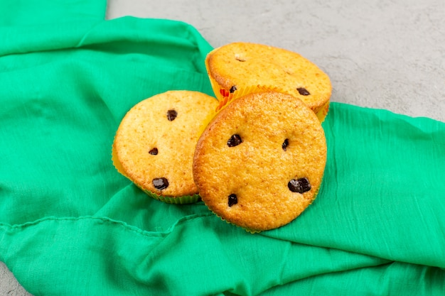 Vue de dessus des gâteaux doux délicieux sur le tissu vert et le sol gris