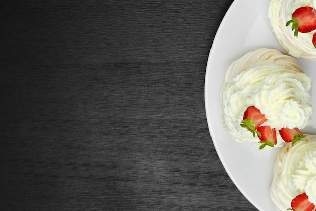 Vue de dessus des gâteaux de meringue avec de la crème et des moitiés de fraises sur la plaque sur un bois noir