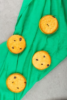 Vue de dessus des gâteaux ronds délicieux sur le tissu vert et gris