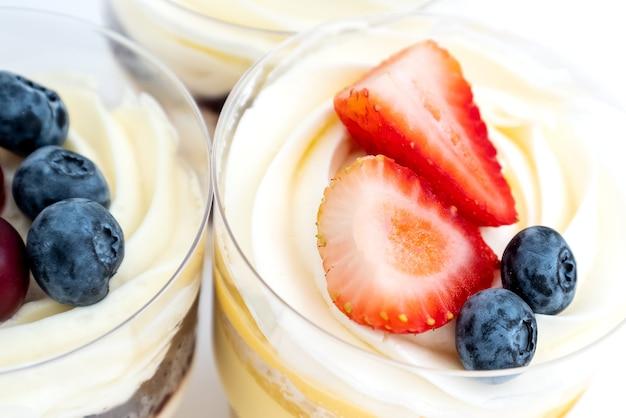 Vue de dessus des gâteaux sucrés à la crème et aux baies fraîches, gros plan