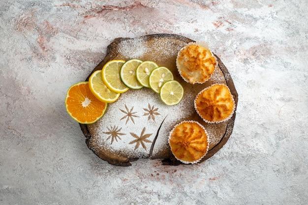 Vue de dessus des gâteaux sucrés avec des tranches de citron sur une surface blanche