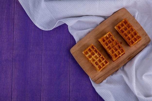 Vue de dessus des gâteaux sur un tissu blanc sur fond violet