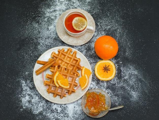 Vue de dessus gaufre dans une assiette avec du thé, orange, confiture de citron sur fond sombre. horizontal
