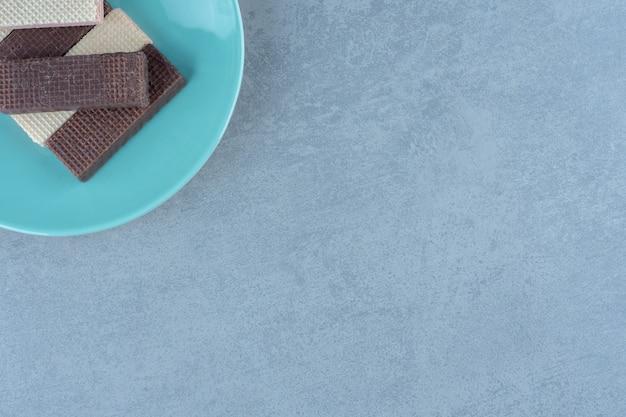 Vue de dessus des gaufres au chocolat et au caramel sur plaque bleue.