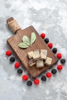 Vue de dessus des gaufres au chocolat avec des confitures de baies sur biscuit gâteau au sucre léger et sucré