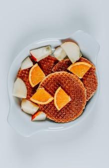 Vue de dessus des gaufres dans un bol avec des oranges et des pommes sur fond blanc. verticale