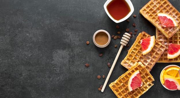 Vue de dessus des gaufres avec une louche au miel et des fruits