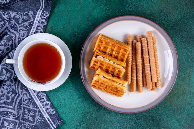 Vue de dessus des gaufres et des petits pains sucrés sur plaque avec une tasse de thé sur vert