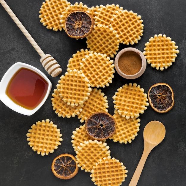 Vue de dessus des gaufres rondes avec une louche au miel et des agrumes séchés
