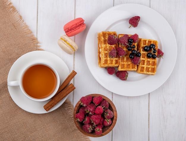 Vue de dessus des gaufres sucrées sur une assiette avec une tasse de thé à la cannelle et aux framboises avec des macarons sur un tableau blanc