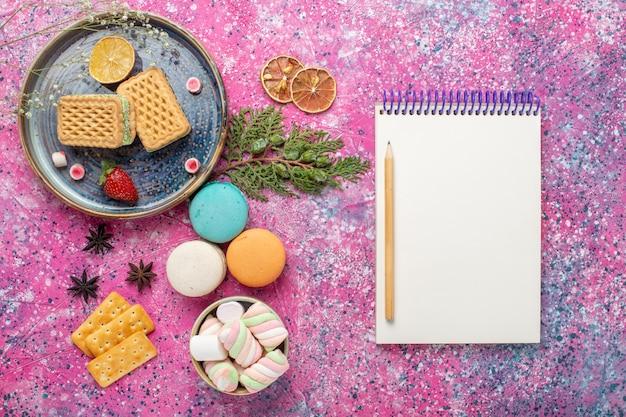 Vue de dessus des gaufres sucrées avec des macarons sur une surface rose clair