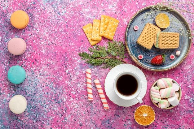 Vue de dessus des gaufres sucrées avec tasse de thé et macarons sur la surface rose