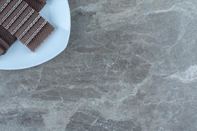 Vue de dessus des gaufrettes au chocolat sur plaque blanche. sur la table grise.