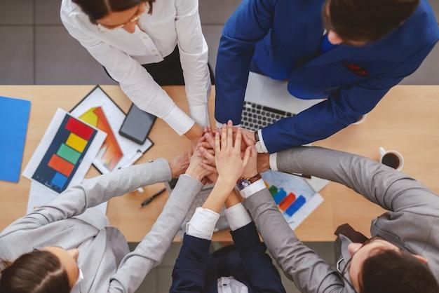 Vue de dessus des gens d'affaires empilant les mains au-dessus du bureau. sur la paperasse de bureau, les ordinateurs portables et les téléphones intelligents. la connaissance est consciente de ce que vous pouvez faire. la sagesse, c'est savoir quand ne pas le faire.
