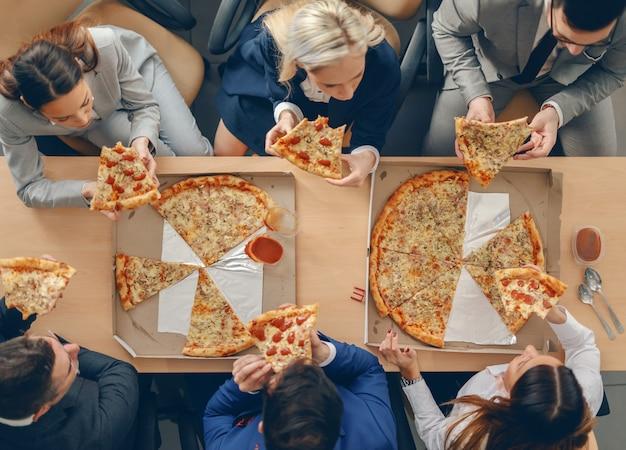 Vue de dessus des gens d'affaires en tenue de soirée assis à table et ayant une pizza pour le déjeuner.