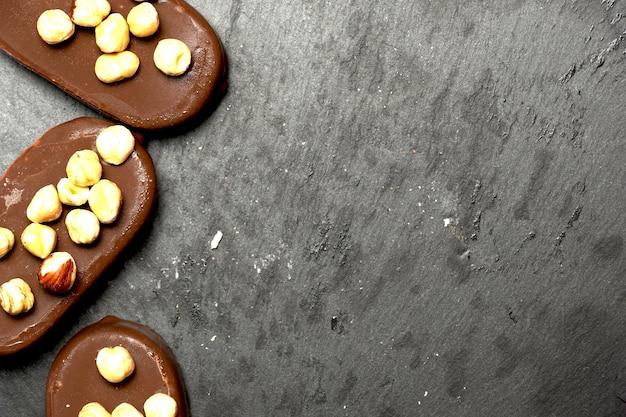 Vue de dessus des glaces au chocolat sur un fond d'ardoise sombre avec un design plat aux noisettes