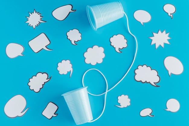 Vue de dessus des gobelets en plastique attachés avec de la ficelle et des bulles de discussion