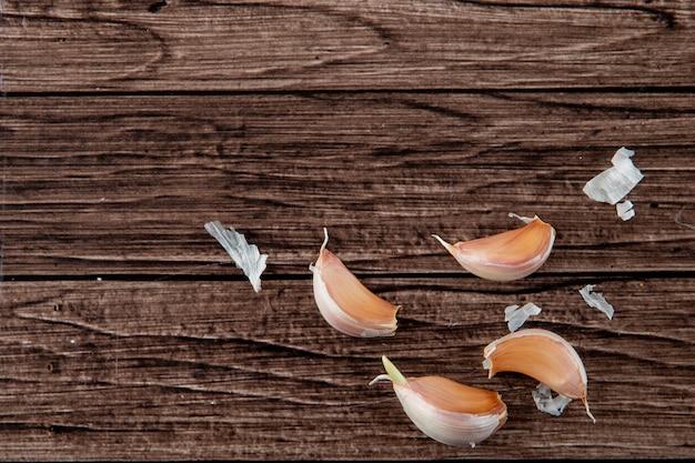 Vue de dessus des gousses d'ail avec peau sur le côté droit et fond en bois avec espace copie