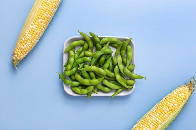 Vue de dessus des gousses de pois sur une assiette avec du maïs