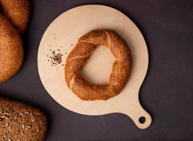 Vue de dessus des graines de bagel et de tournesol sur une planche à découper sur fond marron avec copie espace
