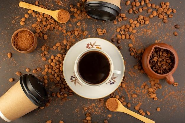 Une vue de dessus des graines de café brun avec des barres de chocolat et une tasse de café