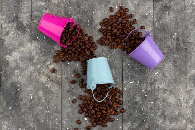 Vue de dessus des graines de café brun à l'intérieur et à l'extérieur des pots colorés sur le sol gris