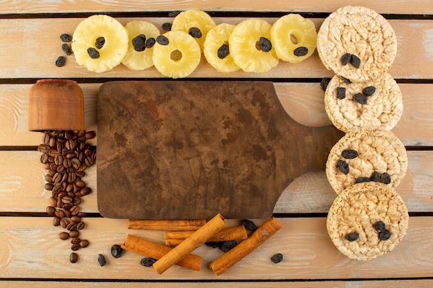 Une vue de dessus des graines de café avec de la cannelle de table d'ananas séché et des craquelins sur la table rustique crème café graine photo grain