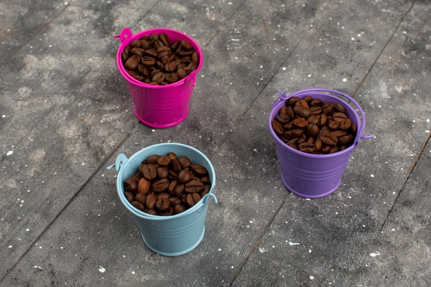 Vue de dessus des graines de café marron à l'intérieur de pots multicolores sur le sol gris