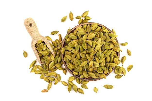 Vue de dessus sur les graines de cardamome isolés dans une assiette en bois et cuillère isolé