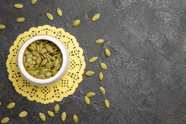 Vue de dessus des graines de citrouille fraîches sur la couleur de la graine de fond sombre de nombreux granulés de citrouille