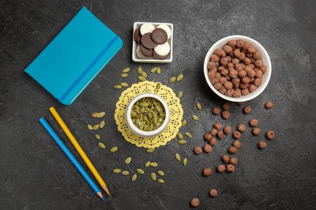 Vue de dessus des graines de citrouille fraîches avec des flocons de chocolat et des biscuits sur fond gris