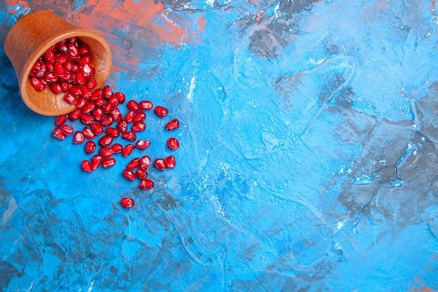Vue de dessus des graines de grenade dans un petit bol en bois sur fond bleu avec place libre