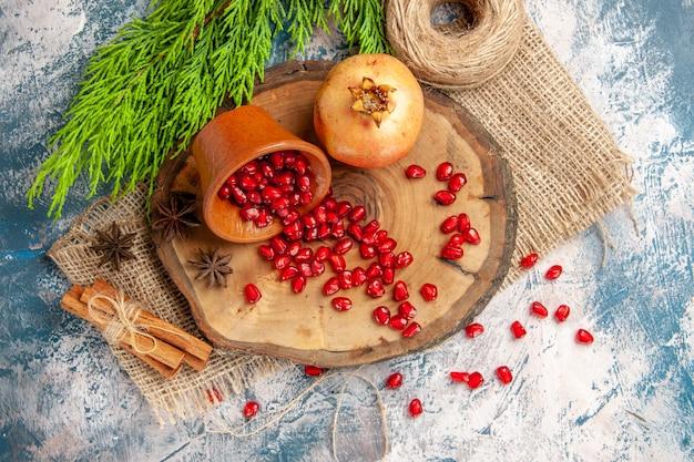 Vue de dessus des graines de grenade dispersées dans un bol sur une planche de bois d'arbre fil de paille graines d'anis à la cannelle sur une surface bleu-blanc