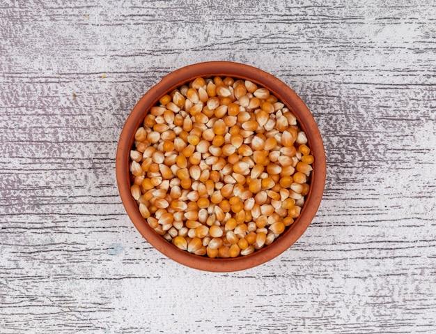 Vue de dessus des graines de pop-corn dans un bol sur l'horizontale en bois blanc