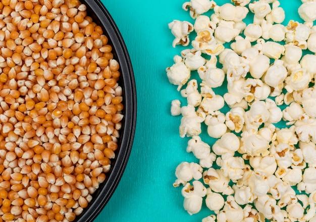 Vue de dessus des graines de pop-corn dans un moule en métal noir à gauche et préparé à droite sur la surface bleue horizontale