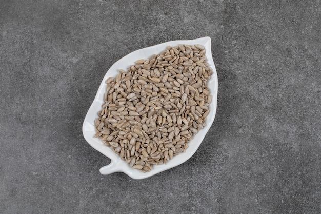 Vue de dessus des graines de tournesol fraîches et saines sur une plaque blanche