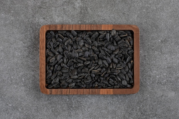 Vue de dessus des graines de tournesol noires sur une plaque en bois sur une surface grise