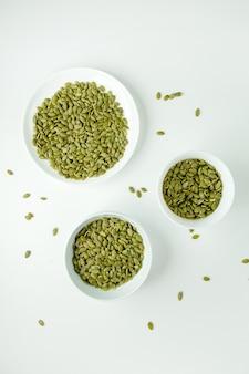 Une vue de dessus les graines vertes salées à l'intérieur de plaques blanches isolées sur le blanc