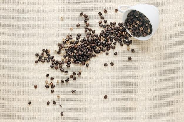 Vue de dessus des grains de café crus et torréfiés tombant d'une tasse en céramique