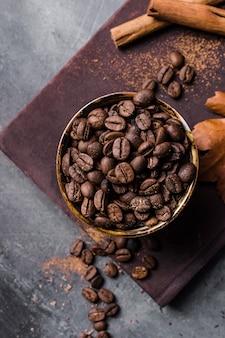 Vue de dessus des grains de café en tasse sur une planche à découper avec de la cannelle