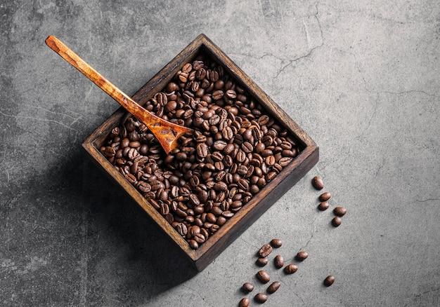 Vue de dessus des grains de café torréfiés dans un récipient carré