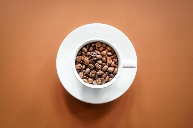 Vue de dessus des grains de café torréfiés dans une tasse à café blanche avec fond marron