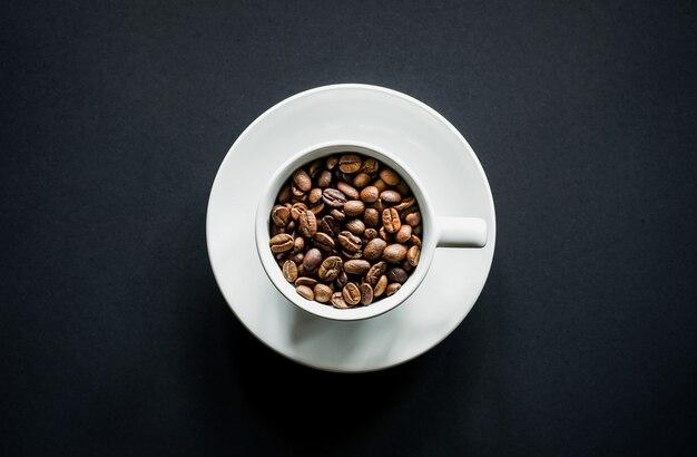 Vue de dessus des grains de café torréfiés dans une tasse à café blanche sur fond noir