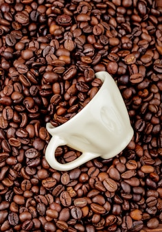Vue de dessus des grains de café torréfiés dispersés dans une tasse en céramique sur les grains de café