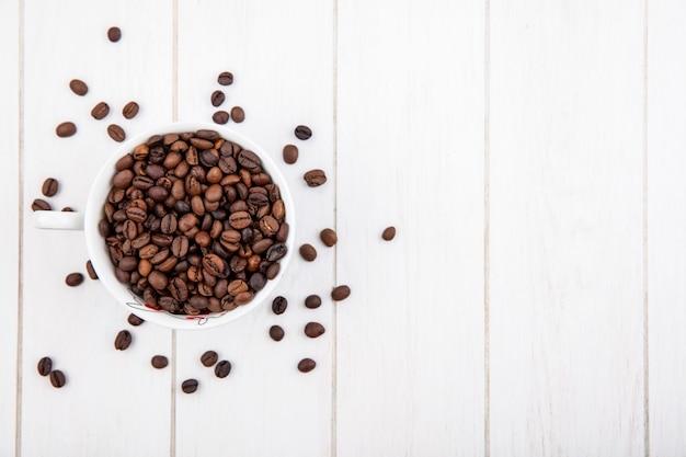 Vue de dessus des grains de café torréfiés foncés sur une tasse blanche sur un fond en bois blanc avec copie espace