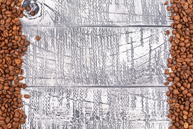 Vue de dessus des grains de café torréfiés sur la surface du bois blanc