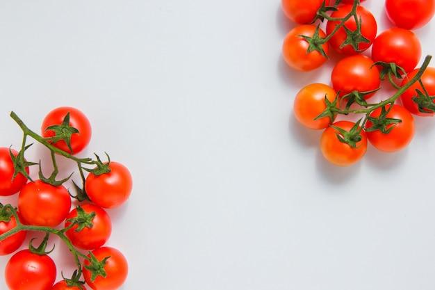 Vue de dessus des grappes de tomates sur fond blanc. espace horizontal pour le texte