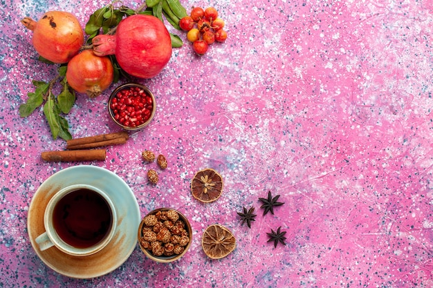 Vue de dessus de la grenade fraîche avec des feuilles vertes et une tasse de thé sur la surface rose