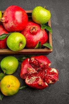 Vue de dessus des grenades fraîches avec des mandarines et des pommes sur la surface sombre des fruits de couleur mûre