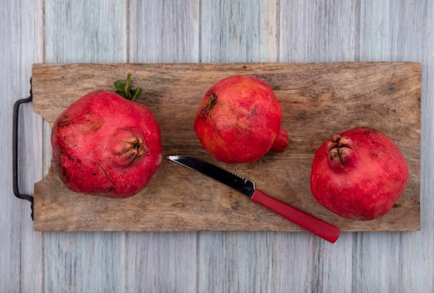 Vue de dessus des grenades fraîches sur une planche de cuisine en bois avec un couteau rouge sur un fond en bois gris
